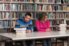 Studente maschio confuso Reading Many Books per esame Fotografia Stock Libera da Diritti