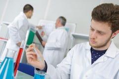 Studente maschio del chimico che esegue esperimento Immagini Stock