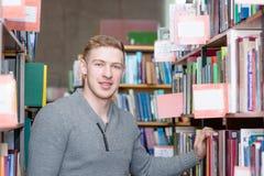 Studente maschio del ritratto in biblioteca Fotografie Stock Libere da Diritti
