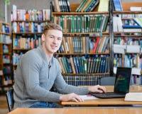 Studente maschio del ritratto con il computer portatile nella biblioteca universitaria Fotografia Stock Libera da Diritti