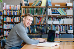 Studente maschio del ritratto con il computer portatile nella biblioteca universitaria Fotografie Stock