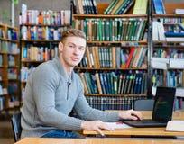 Studente maschio del ritratto con il computer portatile nella biblioteca universitaria Immagine Stock