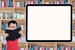 Studente maschio della scuola primaria in biblioteca Fotografia Stock Libera da Diritti