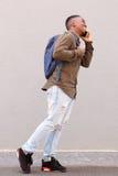 Studente maschio felice che cammina con il telefono cellulare e la borsa Fotografie Stock Libere da Diritti