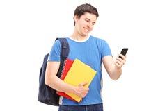 Studente maschio felice che esamina il suo telefono cellulare Fotografie Stock Libere da Diritti