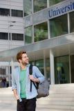 Studente maschio felice che sta sulla città universitaria con la borsa Immagini Stock