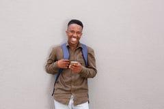 Studente maschio felice con il telefono cellulare della tenuta della borsa Fotografie Stock