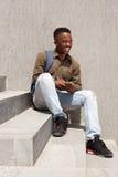 Studente maschio felice con la borsa che si siede sui punti con il telefono cellulare Fotografia Stock Libera da Diritti