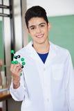 Studente maschio Holding Molecular Structure in laboratorio Fotografia Stock