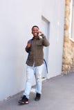 Studente maschio nero sorridente che cammina e che parla sul telefono cellulare Fotografia Stock
