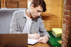 Studente maschio pensieroso che fa piano della preparazione per gli esami, scrivente gli scopi in blocco note mentre sedendosi in Fotografie Stock
