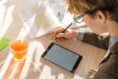 Studente maschio in rivestimento di tweed che fa assegnazione di compito al caffè durante il tempo del pranzo Fotografia Stock Libera da Diritti