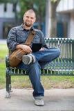 Studente maschio sicuro Sitting On Bench alla città universitaria Fotografie Stock Libere da Diritti
