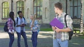 Studente maschio solo che esamina i compagni di classe di risata felici che stanno istituto universitario vicino stock footage