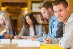 Studente maschio sorridente con gli amici allo scrittorio delle biblioteche Immagini Stock