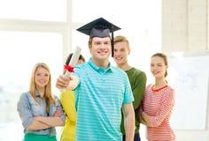 Studente maschio sorridente con il diploma ed il angolo-cappuccio Fotografie Stock Libere da Diritti