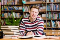 Studente maschio sorridente con il libro aperto che lavora in una biblioteca Fotografia Stock Libera da Diritti