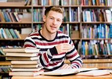 Studente maschio sorridente con il libro aperto che lavora in una biblioteca Fotografia Stock