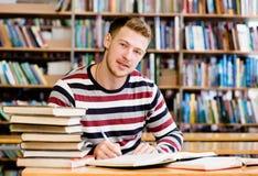 Studente maschio sorridente con il libro aperto che lavora in una biblioteca Immagine Stock Libera da Diritti