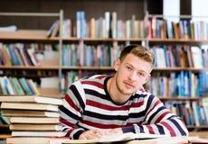 Studente maschio sorridente con il libro aperto che lavora in una biblioteca Immagini Stock