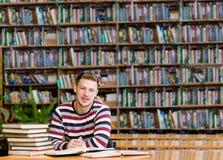Studente maschio sorridente con il libro aperto che lavora in una biblioteca Fotografie Stock