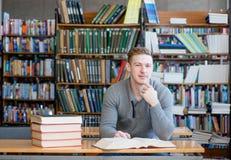 Studente maschio sorridente con il libro aperto che lavora in una biblioteca Fotografie Stock Libere da Diritti