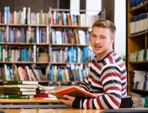 Studente maschio sorridente con il libro aperto che lavora in una biblioteca e nell'esame della macchina fotografica Fotografia Stock