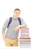 Studente maschio sorridente con la borsa di scuola che posa su un mucchio dei libri Fotografia Stock