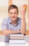 Studente maschio sorridente con la pila di libri Fotografia Stock Libera da Diritti