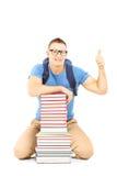 Studente maschio sorridente su un mucchio dei libri che danno pollice su Fotografie Stock