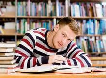 Studente maschio stanco con il libro aperto che lavora in una biblioteca Fotografie Stock