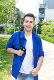 Studente maschio sulla città universitaria che cammina alla macchina fotografica Immagini Stock Libere da Diritti