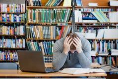 Studente maschio triste nella biblioteca universitaria Fotografia Stock