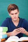 Studente maschio Using Cellphone fotografie stock libere da diritti