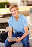 Studente maschio Using Digital Tablet della High School all'aperto Immagini Stock