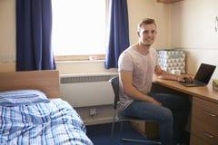 Studente maschio Working In Bedroom della sistemazione della città universitaria immagine stock libera da diritti