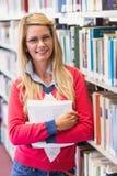 Studente maturo in biblioteca che sorride alla macchina fotografica Immagini Stock Libere da Diritti