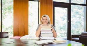 Studente maturo biondo sorridente con la pila di libri Fotografia Stock Libera da Diritti