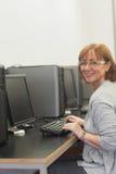 Studente maturo che lavora con un computer che si siede nel centro di calcolo Fotografia Stock Libera da Diritti