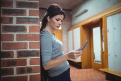 Studente maturo che utilizza telefono cellulare nello spogliatoio Fotografie Stock