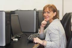 Studente maturo femminile allegro che si siede nella classe del computer Immagini Stock