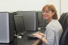 Studente maturo femminile sorridente che per mezzo di un computer Fotografie Stock