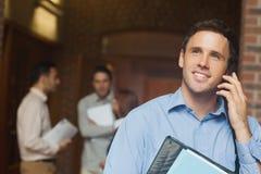 Studente maturo maschio attraente che telefona sul corridoio Immagine Stock