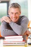 Studente maturo maschio Studying In Classroom con i libri Fotografie Stock Libere da Diritti