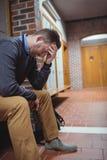 Studente maturo sollecitato che si siede nello spogliatoio Fotografia Stock Libera da Diritti