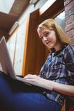 Studente messo a fuoco che si siede sul pavimento contro la parete facendo uso del computer portatile Fotografie Stock Libere da Diritti