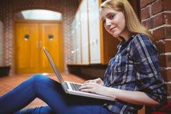 Studente messo a fuoco che si siede sul pavimento contro la parete facendo uso del computer portatile Immagini Stock Libere da Diritti