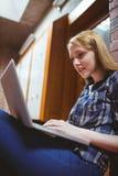 Studente messo a fuoco che si siede sul pavimento contro la parete facendo uso del computer portatile Immagini Stock