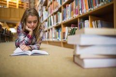 Studente messo a fuoco grazioso che si trova sul libro di lettura del pavimento delle biblioteche Immagine Stock