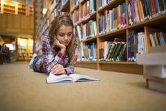 Studente messo a fuoco grazioso che si trova sul libro di lettura del pavimento delle biblioteche Fotografie Stock Libere da Diritti